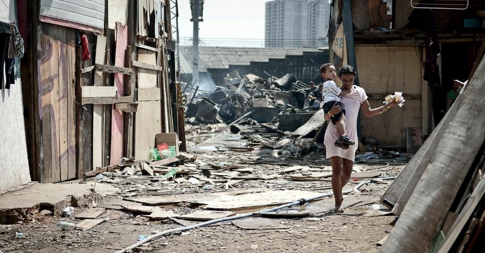 18.set.2012 - Com uma criança no colo, mulher anda em meio aos destroços da favela do Moinho, na região central de São Paulo, um dia após o incêndio que provocou a morte de uma pessoa e deixou cerca de 50 famílias desabrigadas. É a segunda vez em menos de um ano que a comunidade, erguida sob o Viaduto Orlando Murgel, é atingida por um incêndio