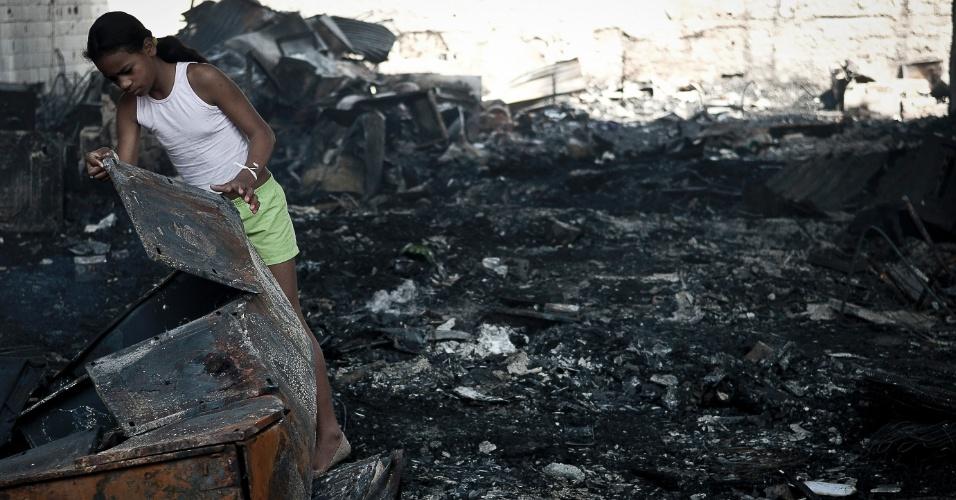 18.set.2012 - Menina ajuda na limpeza da favela do Moinho, na região central de São Paulo, um dia após o incêndio que provocou a morte de uma pessoa e deixou cerca de 50 famílias desabrigadas. É a segunda vez em menos de um ano que a comunidade, erguida sob o Viaduto Orlando Murgel, é atingida por um incêndio
