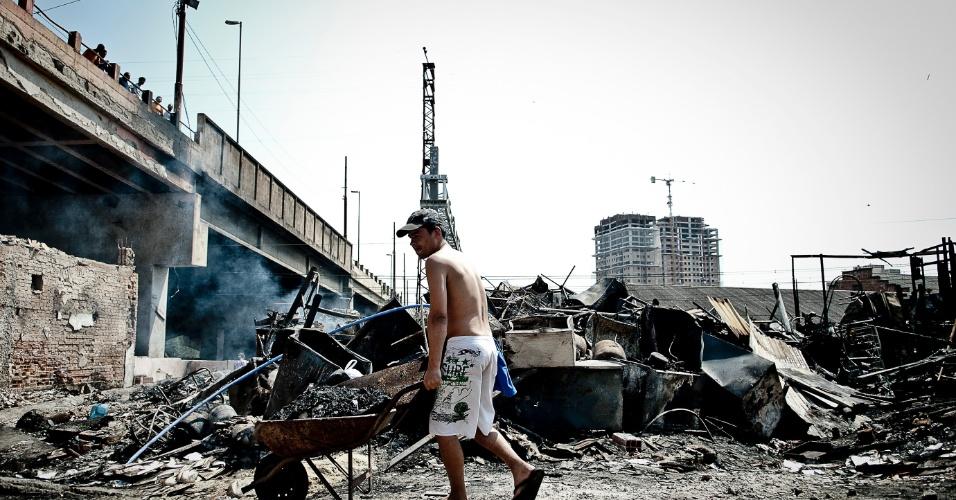 18.set.2012 - Morador da favela do Moinho ajuda na limpeza da favela do Moinho, na região central de São Paulo, um dia após o incêndio que provocou a morte de uma pessoa e deixou cerca de 50 famílias desabrigadas. É a segunda vez em menos de um ano que a comunidade, erguida sob o Viaduto Orlando Murgel, é atingida por um incêndio