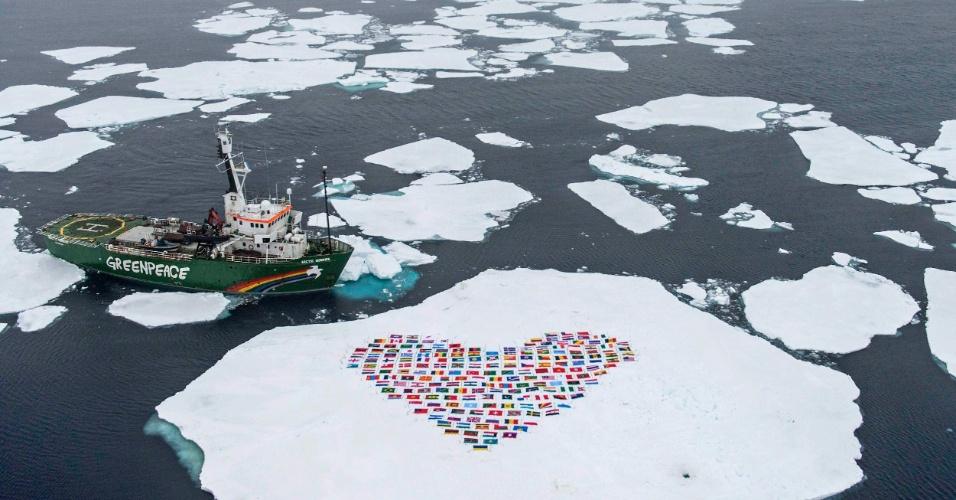 19.set.2012 - Bandeiras dos 193 países que integram a ONU são colocadas na neve em frente navio Sunrise, do Greenpeace