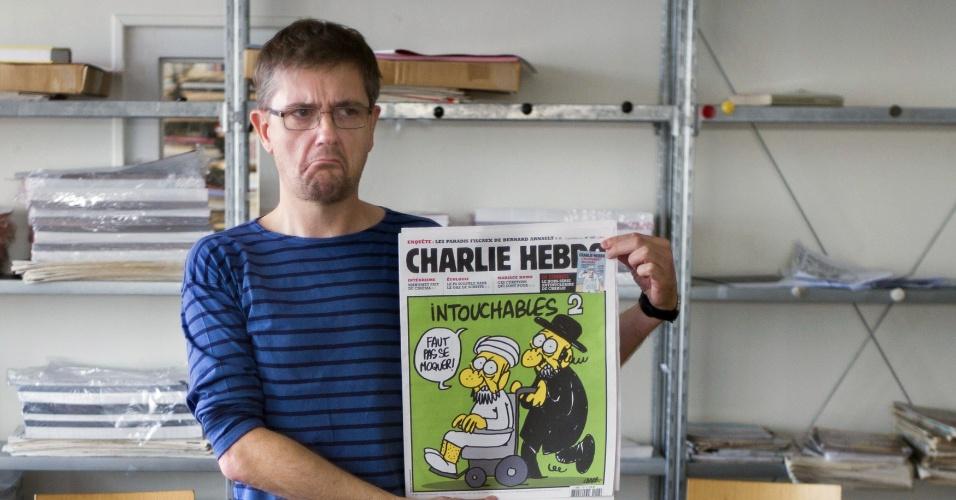 19.set.2012 - O cartunista francês Charb, diretor de publicação de que publicou cartuns com o profeta Maomé, posa para fotos em seu escritório em Paris, na França