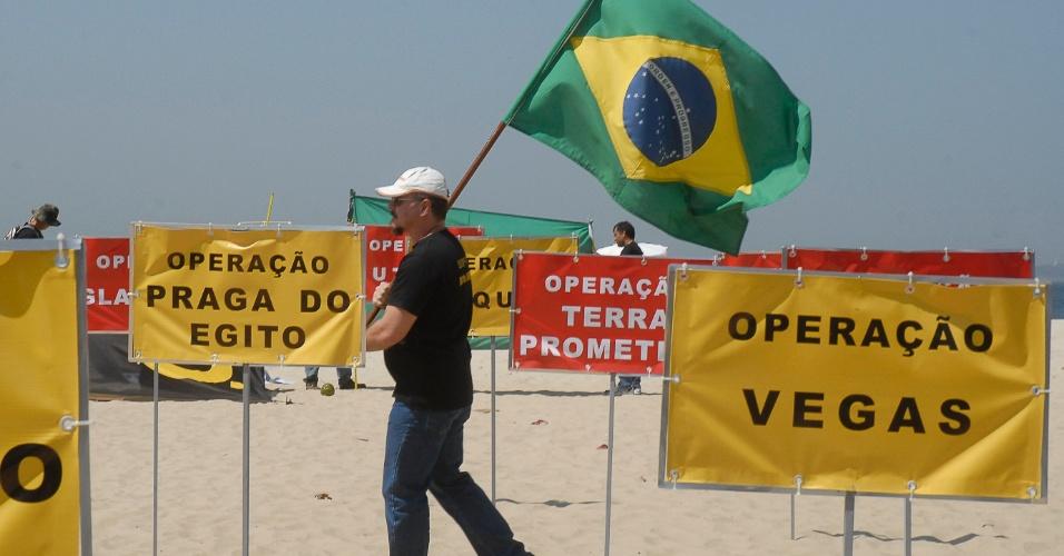19.set.2012 - Homem carrega bandeira do Brasil durante manifestação dos policiais federais em greve na praia de Copacabana. Os policiais fixaram na areia 30 placas com os nomes das principais operações da PF no país