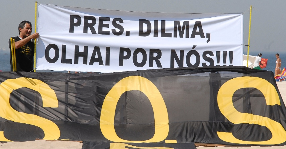 19.set.2012 - Homem segura faixa com mensagem para a presidente Dilma Rousseff durante manifestação dos policiais federais em greve na praia de Copacabana. Os policiais fixaram na areia 30 placas com os nomes das principais operações da PF no país