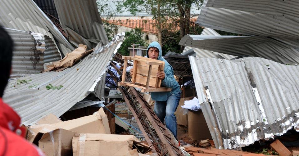 19.set.2012 - Trabalhador tenta recuperar pertences de uma fábrica de alfaiataria destruída por uma tempestade que atingiu a cidade de Mariano Roque Alonso, no Paraguai. Ao menos cinco pessoas morreram e outras 100 ficaram, segundo a Secretaria de Emergência Nacional (SEN)