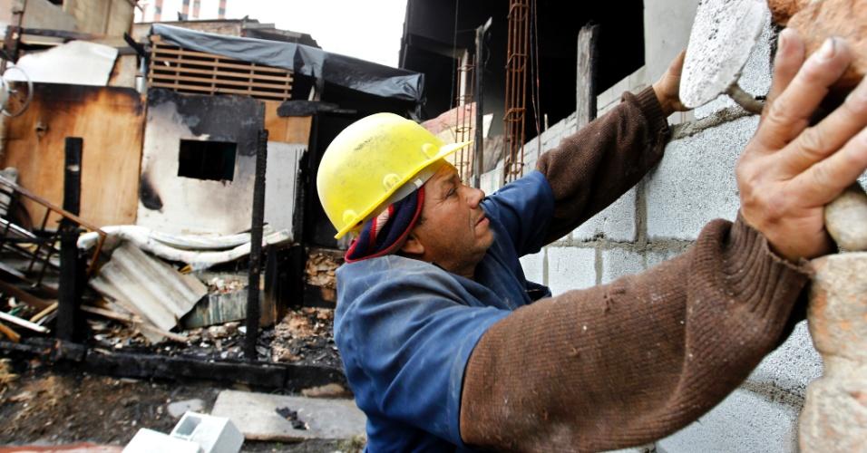 20.set.2012 - Funcionário da Prefeitura constrói muro para inibir a construção de novos barracos na favela do Moinho, no centro de São Paulo