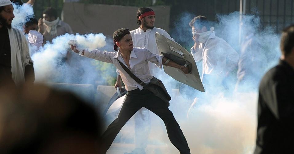 20.set.2012 - Manifestante paquistanês atira bomba de gás lacrimogêneo em protesto contra filme anti-Islã