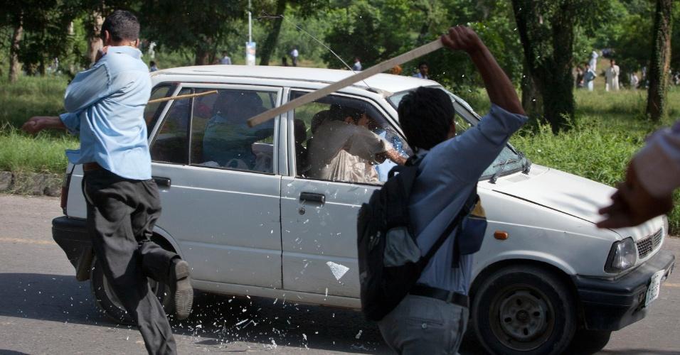 20.set.2012 - Manifestantes quebram vidros de carro em protesto contra filme anti-Islã em Islamabad, no Paquistão