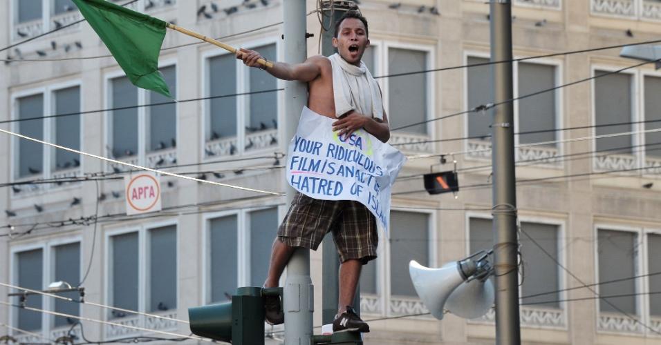 23.set.2012 - Manifestante segura cartaz em cima de semáforo perto da embaixada dos EUA em Atenas, na Grécia, neste domingo (23). O protesto é contra o filme que denigre a imagem do profeta Maomé. A polícia usou gás lacrimogêneo para dispersar alguns manifestantes