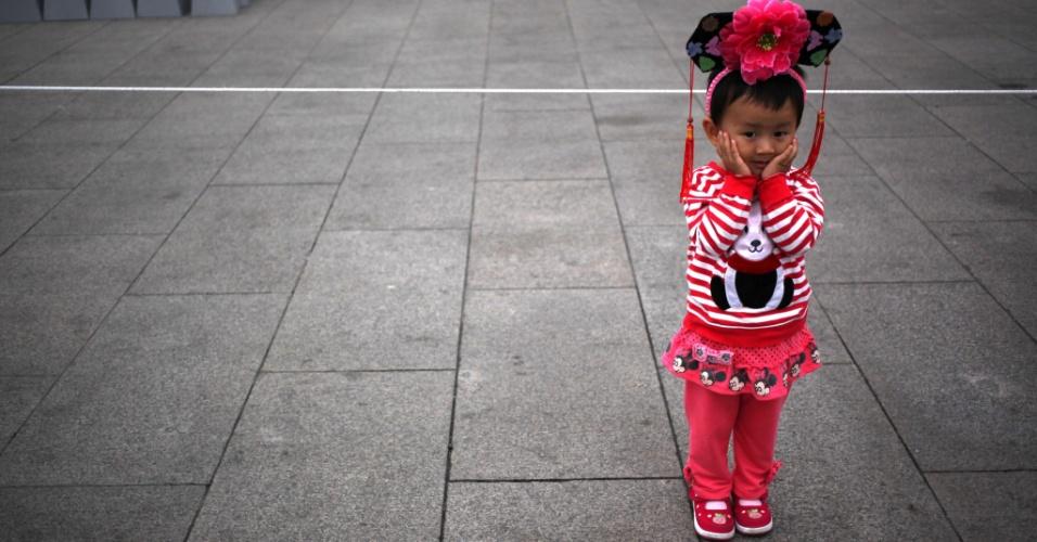24.set.2012 - Menina chinesa aguarda preparativos para o Dia Nacional em Pequim, na China, que acontece em outubro