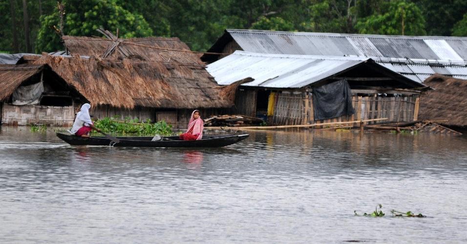 24.set.2012 - Moradores usam barco para se locomover por área inundada na aldeia Kaziranga, próximo de Guwahati, capital do estado indiano de Assam