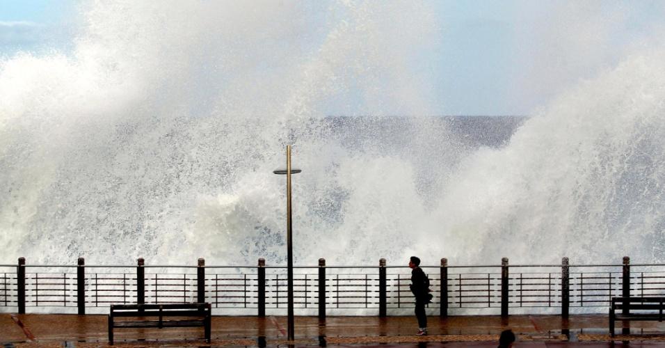 24.set.2012 - Mulher caminha em San Sebástian, na Espanha, enquanto onda atinge orla