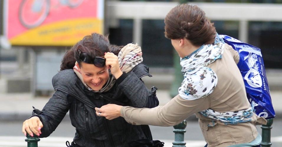 24.set.2012 - Mulheres tentam se manter em pé durante forte rajada de vento, em Bruxelas, Bélgica