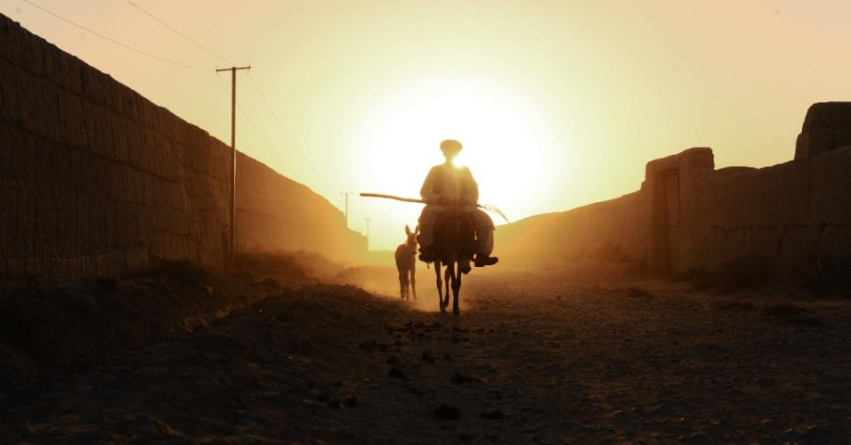 24.set.2012 Um homem montado em seu burro, passa em uma estrada de terra no distrito de Zadyan província de Balkh, no Afeganistão