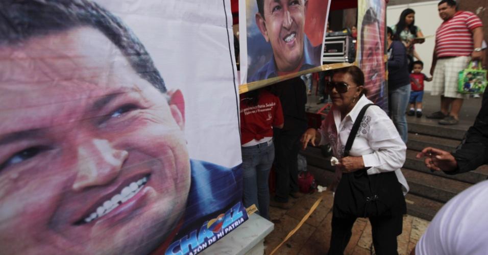 25.set.2012 - Mulher caminha por cartazes do presidente e candidato à reeleição Hugo Chávez, em Caracas, na Venezuela. Em pesquisa divulgada recentemente, Chávez tem vantagem de 10 pontos sobre seu rival Henrique Capriles. As eleições estão marcadas para o dia 7 de outubro