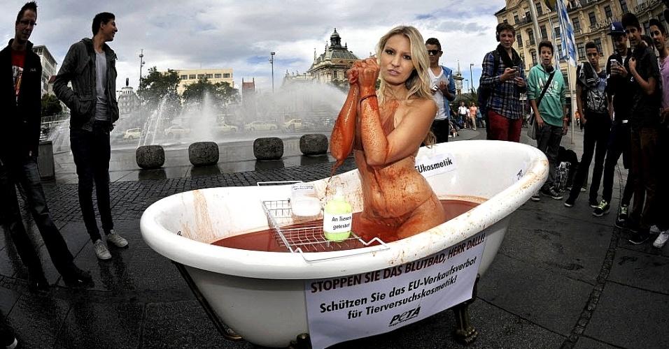 26.set.2012 - Uma das garotas da Playboy, Doreen Seidel, posa seminua dentro de banheira com sangue falso durante protesto da organização que defende os direitos dos animais Peta, em Munique, na Alemanha. O protesto é contra o afrouxamento da proibição europeia de vender cosméticos que se utilizaram de experimentos em animais