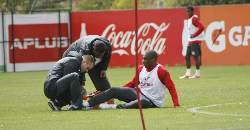 Zagueiro Juan recebe atendimento após torcer o tornozelo direito em treino do Inter (26/09/12)