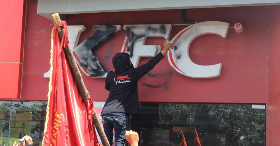 27.set.2012 - Estudantes picham fachada de restaurante de famosa rede americana de fast-food nesta quinta-feira (27) em Kendari, na Indonésia, durante protesto contra filme anti-islã produzido nos Estados Unidos