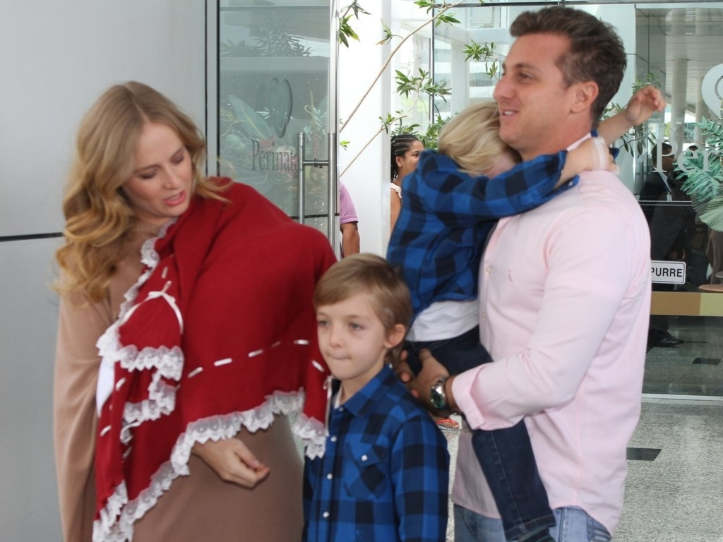 Acompanhados dos filhos Joaquim e Benício, Angélica e Luciano Huck deixam a maternidade com a filha recém-nascida Eva.