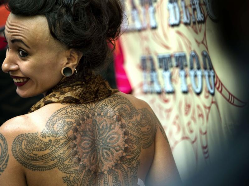 28.set.2012 - Uma mulher se vira para ver no espelho o resultado da sessão de tatuagem, nesta sexta-feira (28), durante o 8° London International Tattoo, convenção que vai de 28 a 30 de setembro em Londres em 28 de setembro de 2012. Tatuadores do mundo se reúnem em Londres para o evento anual