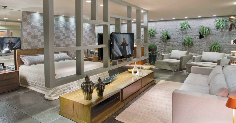 As arquitetas Carolina Magalhães e Tatiana Pandolfi projetaram os 55m² do Quarto do Casal. No ambiente, uma divisória desenhada pelas profissionais segmenta os espaços de dormir e descansar e sustenta TV's de ambos os lados. A Casa Cor Brasília fica aberta ao público de 29 de setembro a 06 de novembro de 2012