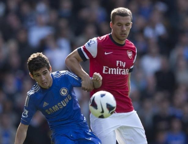 29.set.2012 - O meia brasileiro Oscar (esq), do Chelsea, tenta fugir da marcação de Podolski, do Arsenal, em jogo da Liga dos Campeões
