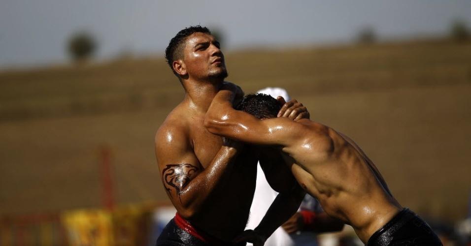 Encharcados de óleo, competidores se enfrentam numa espécie de luta olímpica, em evento na Bulgária