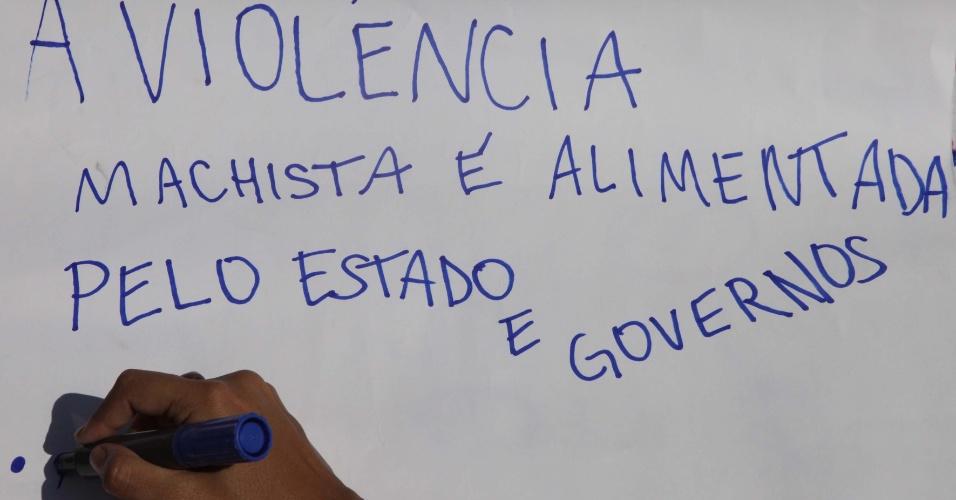 Manifestante redige cartaz para uso na Marcha das Vadias em Santos (SP)