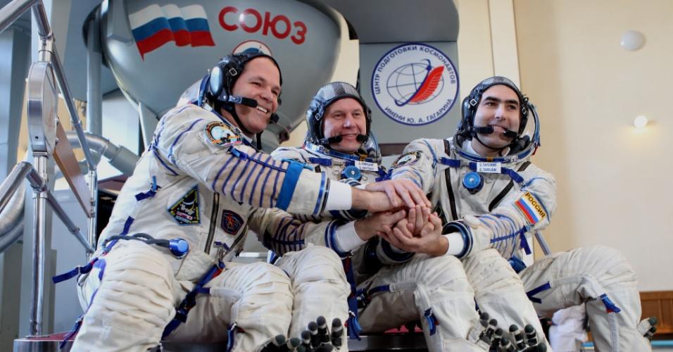 01.out.2012 - Os astronautas Kevin Ford, Oleg Novitskiy e Evgeny Tarelkin, da esquerda para direita, posam para fotos na frente da nave Soyuz após última sessão de testes qualificatórios no centro de treinamento Cosmonauta Gagarin, na Rússia. O trio viajará ao espaço no próximo dia 23 para passar para cinco meses na Estação Espacial Internacional (ISS, na sigla em inglês)