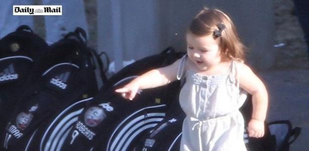 Harper, filha de David e Victoria Beckham brinca com uma bola durante um jogo de um de seus irmãos