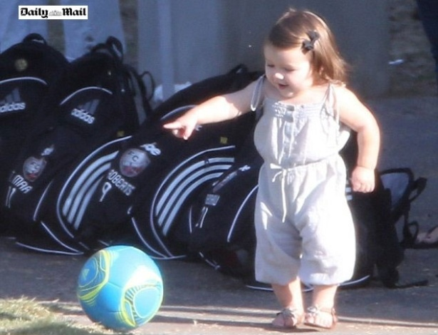 Harper, filha de David e Victoria Beckham brinca com uma bola durante um jogo de um de seus irmos 