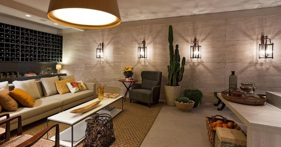 No Estar da Família, assinado pela arquiteta Estela Netto, a luminária principal - em madeira e acrílico leitoso - é combinada às arandelas