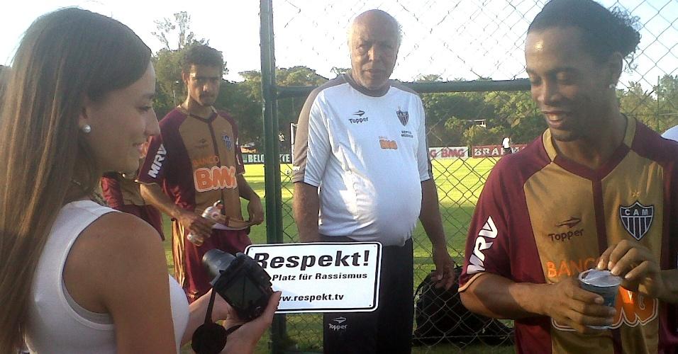 Jornalista Paula Widmer mostra a placa com dizeres contra racismo a Ronaldinho Gaúcho (2/10/2012)