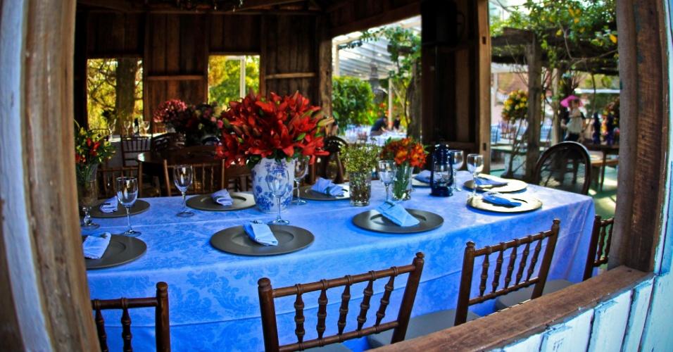 Mesas de jantar decorada com mobiliário de antiquário, com vasos de cerâmica em tom azul e itens de cristal, que dão um toque de elegância ao rústico. Decoração feita pela empresa Cenográphia (www.cenographia.com.br)