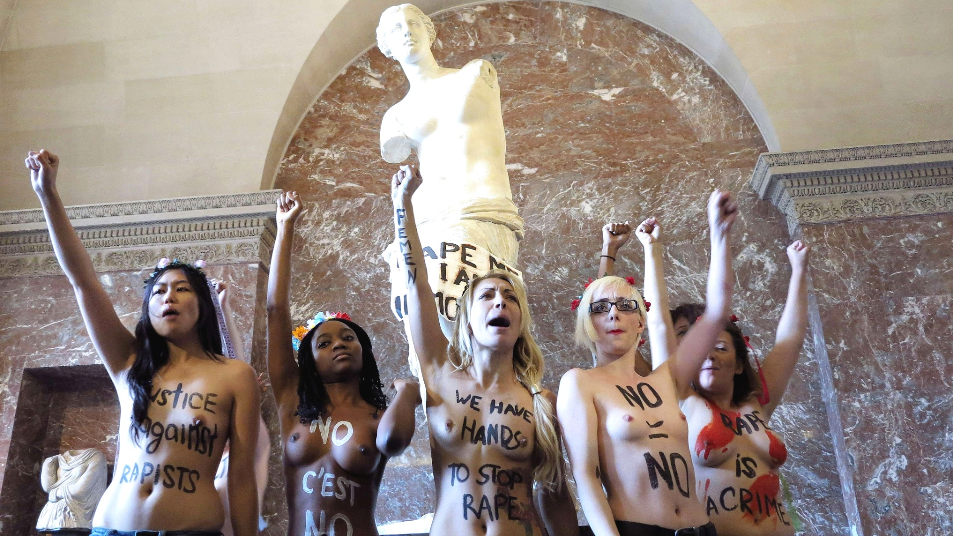 3.out.2012 - Manifestantes do grupo feminista Femen, tiram a roupa nesta quarta-feira (3), em frente  esttua de Venus de Milo, no museu do Louvre, em Paris (Frana), como forma de protesto contra polticas desfavorveis s mulheres
