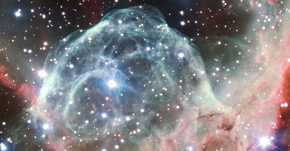 5.out.2012 - Para comemorar seus 50 anos, o Observatório Europeu do Sul (ESO, na sigla em inglês) fez imagens da nebulosa Elmo de Thor, após escolha do público. Também conhecida por NGC 2359, a nuvem de poeira é uma maternidade estelar na constelação Cão Maior, a cerca de 15 anos-luz de distância da Terra.  Sua forma de capacete surgiu a partir do vento da estrela de grande massa (ponto brilhante mais próximo do centro) que se desloca através da nuvem molecular soprada para a bolha cósmica. A estrela também emana radiação e aquece os diferentes gases ao seu redor, reação que dá a nuance de cores na nebulosa