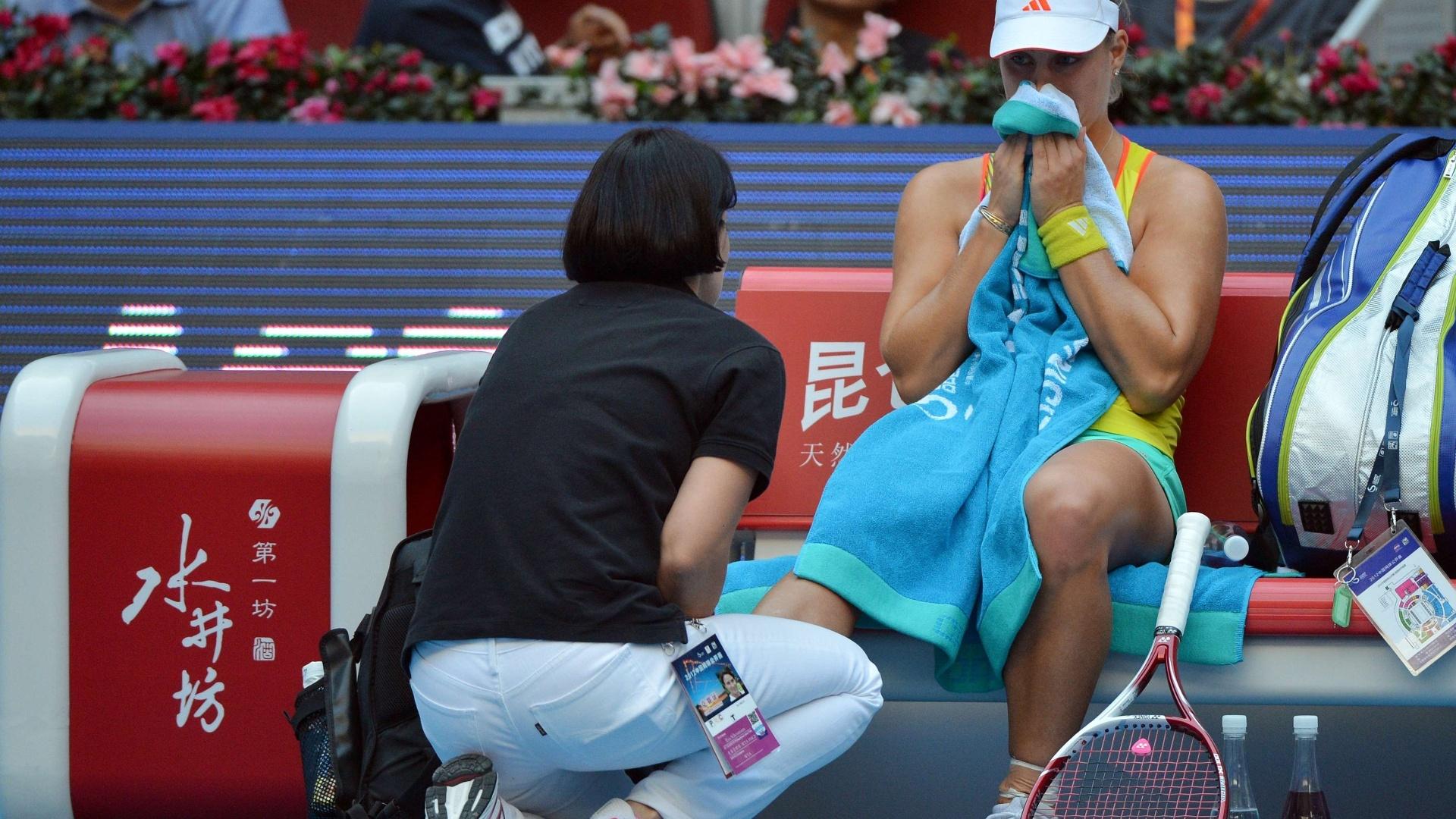 Alemã Angelique Kerber recebe atendimento médico no jogo contra a russa Maria Sharapova. Kerber desistiu do jogo, e Sharapova avançou à semifinal do Torneio de Pequim (05/10/2012)