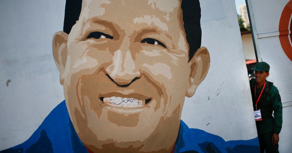 6.out.2012 - Soldado é visto próximo a um portão com a imagem de Hugo Chávez, candidato à reeleição na Venezuela. O presidente Hugo Chávez tenta se reeleger em pleito que vai ser realizado no domingo (8). Pesquisas apontam que o voto dos indecisos definirá o pleito no país latino americano