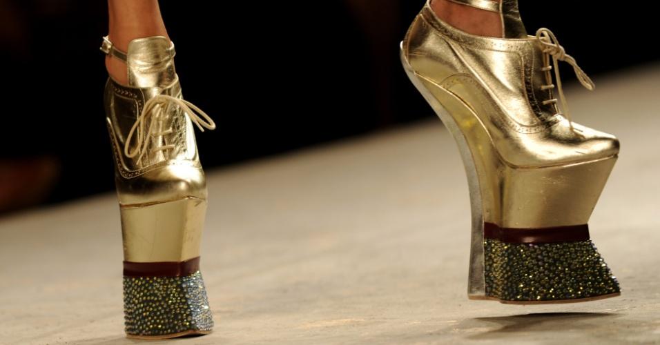 Modelo apresenta sapatos altíssimos sobre solado com forma semelhante a um