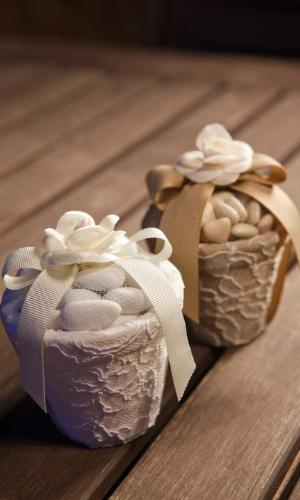 Dragées [amêndoa revestida com açúcar] em vaso de cerâmica forrado com renda francesa e detalhe de flor de tecido; da Jeniffer Bresser (www.jenifferbresser.com.br), a partir de R$ 65 (a unidade). Disponibilidade e preço sujeitos a alterações. Pesquisa realizada em outubro de 2012