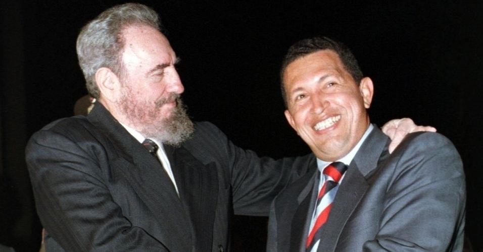 Fidel cumprimenta Hugo Chávez em 1999, quando ele foi eleito pela primeira vez presidente na Venezuela. A parceria entre os dois se aprofundou em 2000, com um acordo que prevê, por parte da ilha, o fornecimento de equipamentos e de profissionais das áreas de saúde, educação e esporte, em troca do petróleo venezuelano