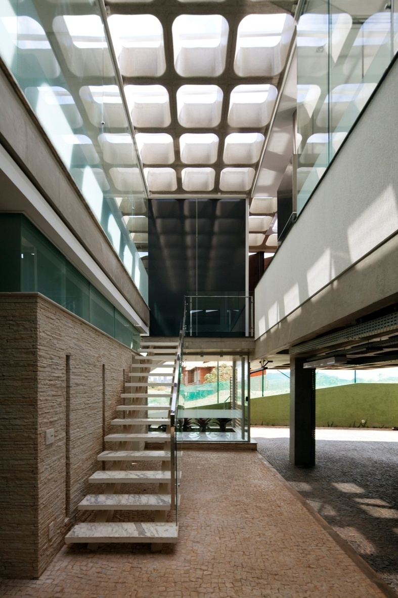 Assim como para a escada de acesso principal, a escadaria secundária que liga a garagem ao volume social da casa é iluminada naturalmente pelas aberturas zenitais da laje