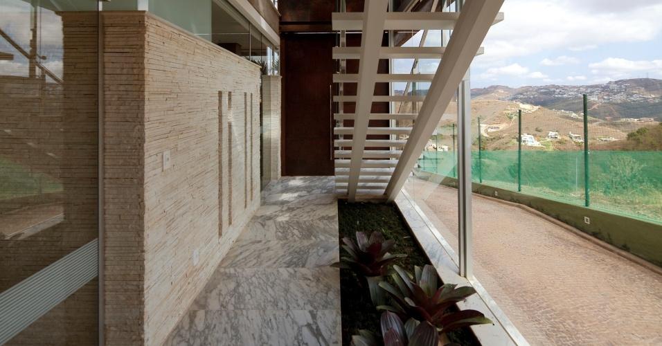 Na foto, uma das escadas de acesso ao pavimento principal da casa NB, em Nova Lima (MG). Com estrutura de metal, a escadaria ganhou paisagismo sob si - com bromélias - e é ladeada por um pano de vidro (à dir.) e uma parede revestida por canjiquinha, à esquerda. O projeto é assinado por Alexandre Brasil e Paula Zasnicoff, do escritório Arquitetos Associados