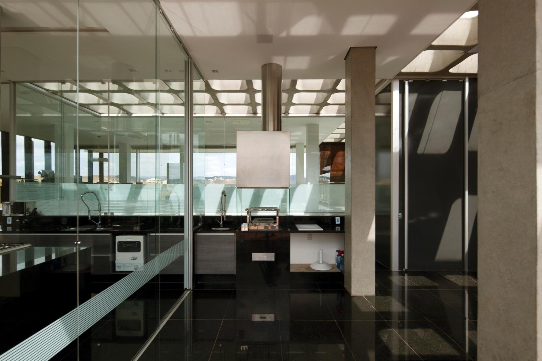 A cozinha da casa NB tem chão revestido por granito preto e - seguindo o padrão do restante da casa - abusa dos vidros. Localizada no volume social e frontal da construção, o ambiente está intimamente ligado à churrasqueira da residência. O projeto arquitetônico é de Alexandre Brasil e Paula Zasnicoff, do escritório Arquitetos Associados