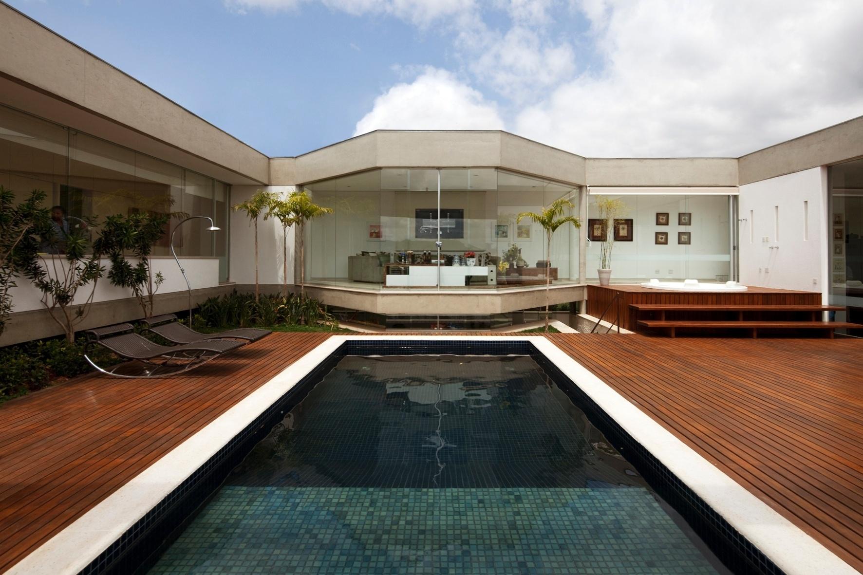 Visto à partir da pérgula: o pátio de lazer e seu amplo deck de madeira. A piscina tem largura que acompanha a sala íntima da residência, na área de circulação, sob a qual está - semi-enterrada - a sala de brincar das crianças. À esquerda, atrás das espreguiçadeiras, está a circulação dos quartos. A casa NB, em Nova Lima (MG), tem projeto de Alexandre Brasil e Paula Zasnicoff, do escritório Arquitetos Associados
