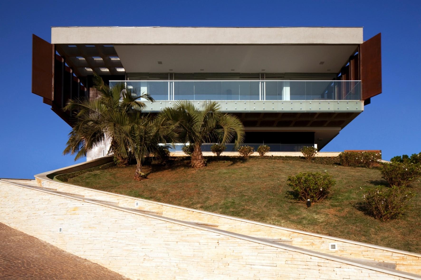 A comprida escada de pedra dá acesso à casa NB, no topo de uma colina, em Nova Lima (MG). Em frente à construção, um jardim  - com paisagismo de Felipe Fontes - reúne palmeiras baixas e pequenos arbustos distribuídos esparsamente. Na fachada frontal, uma varanda ampla abrange a totalidade da largura e é limitada por um guarda-corpo de vidro. O projeto é do escritório Arquitetos Associados, de Belo Horizonte