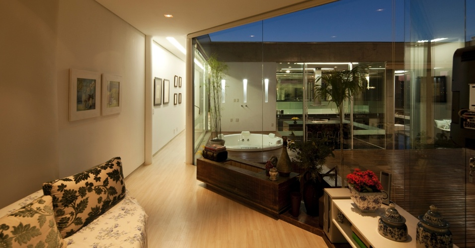 Vista da sala íntima da casa NB, que se integra ao deck de lazer através dos panos de vidro. A residência em Nova Lima (MG), tem projeto de Alexandre Brasil e Paula Zasnicoff, do escritório Arquitetos Associados s