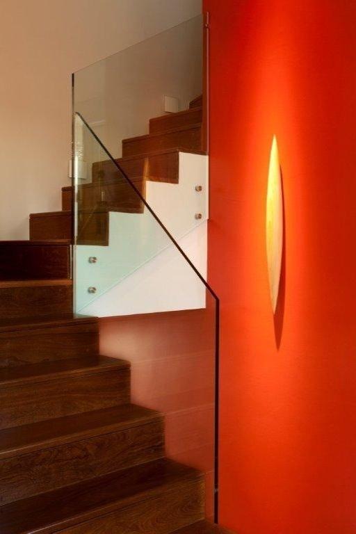 A escada que dá acesso ao pavimento íntimo funciona como elemento escultural: o corrimão original, de ferro, foi substituído por um guarda-corpo de vidro (Guardian) e balizadores auxiliam na iluminação. O diferencial, porém, é o vermelho intenso aplicado a uma das paredes. O projeto de interiores da Casa no Alto de Pinheiros é assinado por Marília Veiga