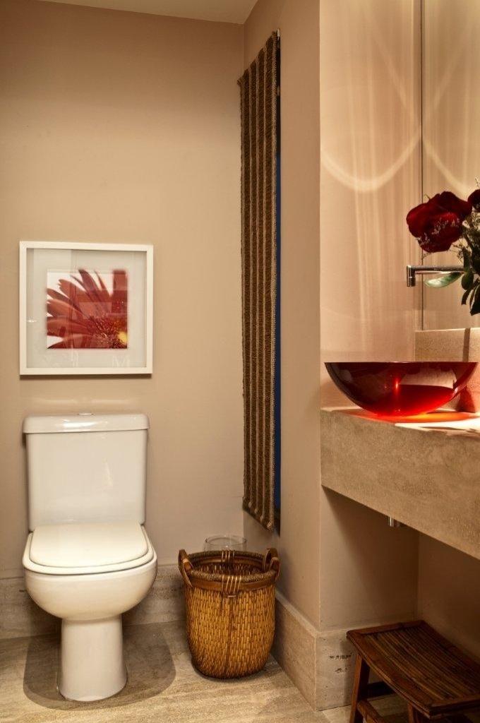 Ainda no piso de entrada, o lavabo foi revestido de mármore travertino romano, com cuba em resina de cor vermelha. Destaque para a bancada, também em travertino, desenhada de maneira a esconder o sifão. Os interiores da Casa no Alto de Pinheiros tem desenho de Marília Veiga