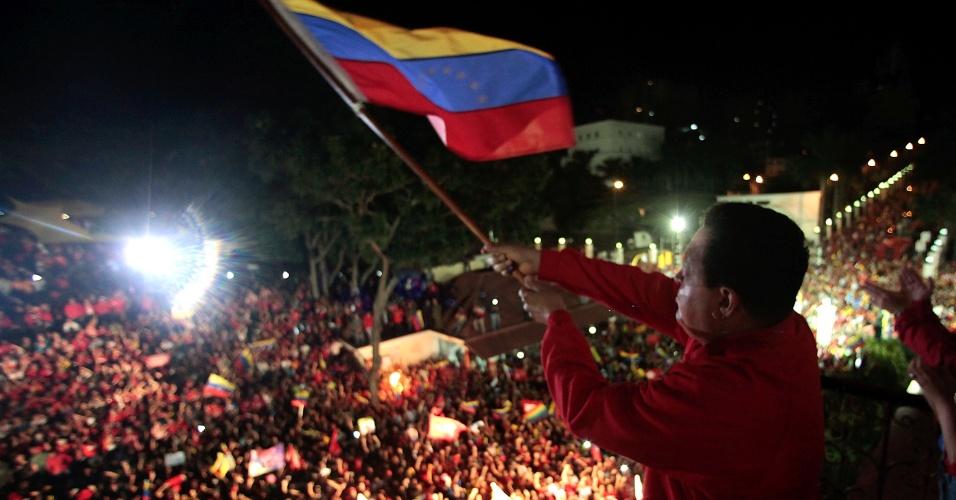 Hugo Chávez balança a bandeira da Venzuela na sacada do palácio de Miraflores