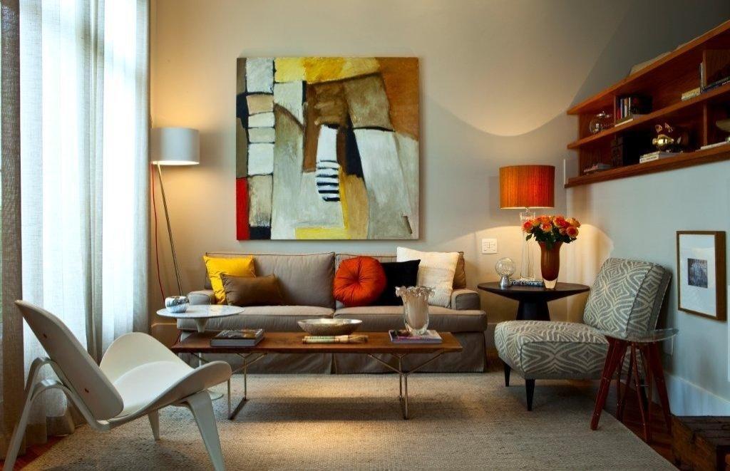 O living - com pé-direito duplo - conta com sofá (Montenapoleone) forrado por sarja (Bauhaus), além de poltrona e almofadas da Empório Beraldin. A mesa de centro, releitura da mesa Bertóia, possui tampo mais rústico e contrasta com a cadeira branca (Empório Vermeil), à esquerda. À direita, sobre o patamar, a estante de madeira desenhada por Marília Veiga - que também assina a decoração da Casa no Alto de PInheiros - foi executada pela marcenaria Takae